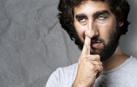 nose picking: portrait of young man with the finger in his nose against a grunge background