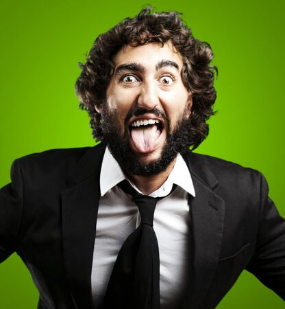 portrait of young man joking and showing the tongue over green background photo