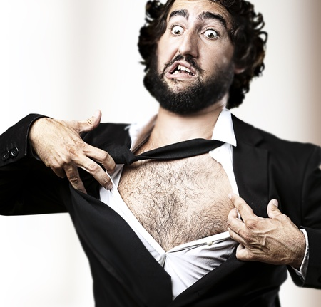 business man with courage and superman concept tearing off his shirt against a abstract background photo