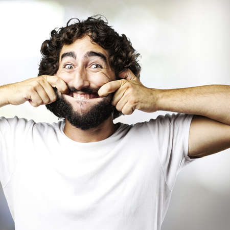 portrait of young man pulling his mouth smiling indoor Stock Photo - 12656708