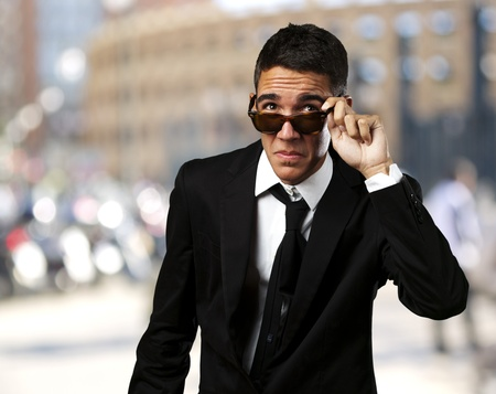 portrait of business man taking off the sunglasses at crowded city photo