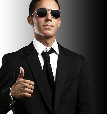 homem: portrait of young business man with sunglasses with thumb up against a yellow background