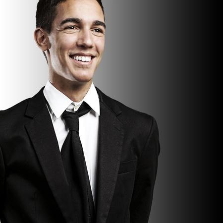 black business men: portrait of young business man smiling against a black background