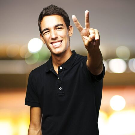 portrait of young man smiling and doing good symbol against a city by night photo