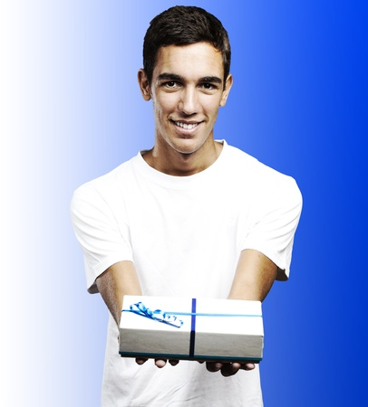 young man smiling and giving a gift against a blue background photo