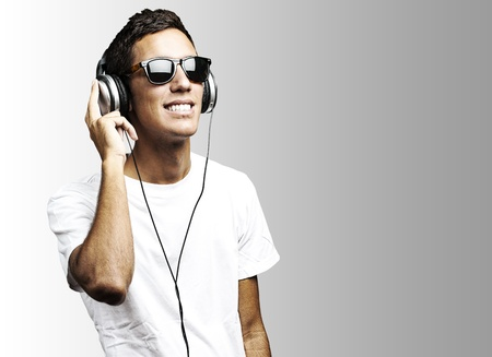 portrait of young man with sunglasses playing to music on a grey background photo
