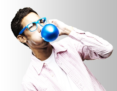 portrait of young man with glasses inflating a blue balloon against a white background photo