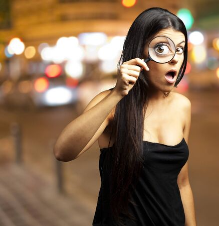 Young woman surprised looking through a magnifying glass at city Stock Photo - 12656833