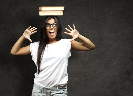 portrait of young woman holding books on her face against a grunge background Stock Photo - 12656841