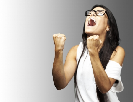 cheering people: portrait of young winner woman with glasses over a grey background