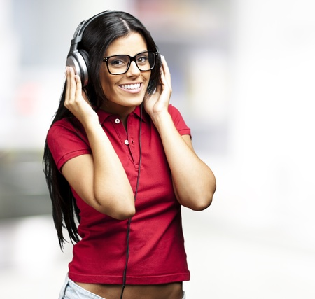 portrait of young woman listening to music against a abstract background Stock Photo - 12656716