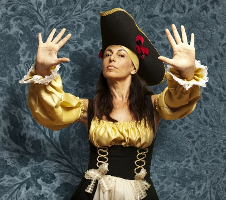 portrait of pirate woman gesturing stop against a vintage background photo