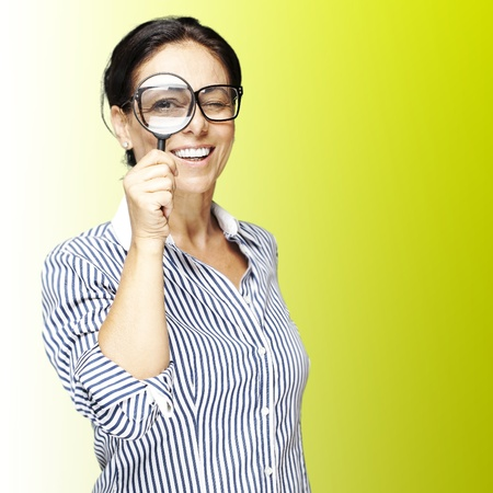 portrait of woman with looking through a magnifying glass against a green background Stock Photo - 12656702
