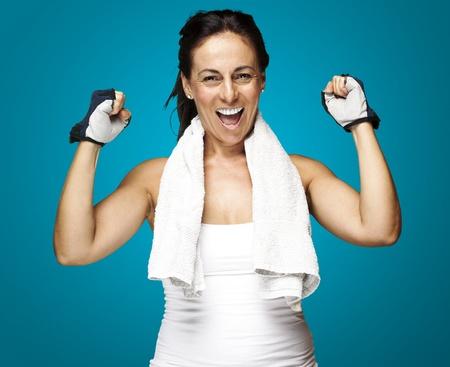 mujer cuerpo completo: mujer joven haciendo un gesto deportivo ganador contra un fondo azul