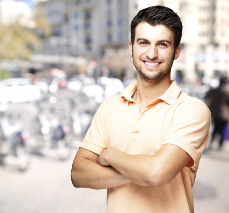 crossed: young man smiling against a street background