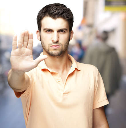 stop gesture: young man doing a stop gesture against a street background