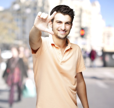 good looks: young man smiling and doing a symbol against a street background