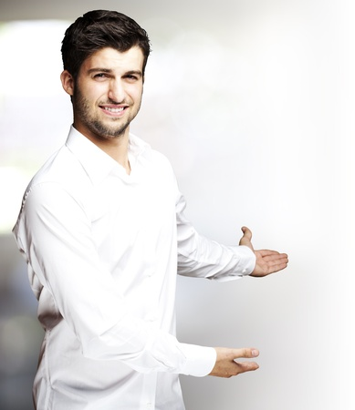 gesturing: portrait of a handsome young man gesturing welcome indoor Stock Photo