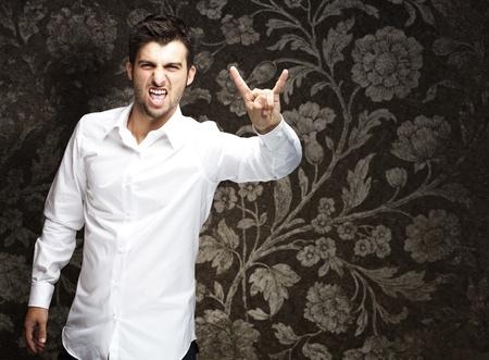 young man doing a rock gesture against a vintage background photo