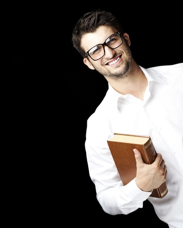 portrait of young student with glasses holding a book against a black background photo