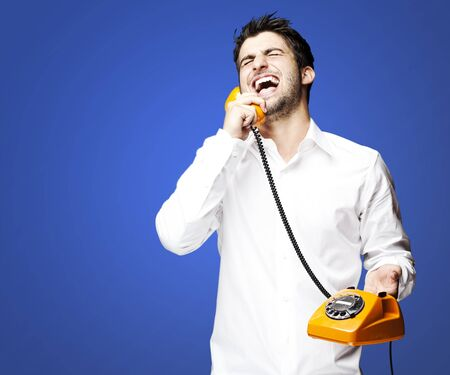 portrait of young man talking using vintage telephone laughing over blue background photo
