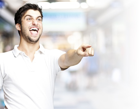 portrait of a handsome young man pointing and joking at a crowded place photo