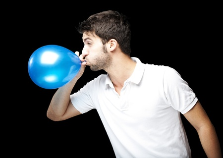 portrait of young man blowing a balloon over black background photo