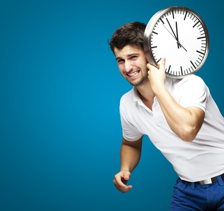 against the clock: young man holding a clock on his back against a blue background