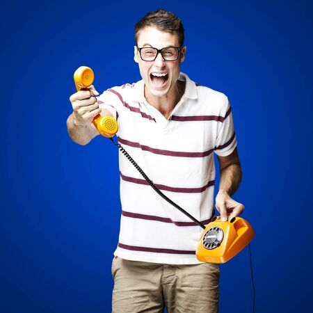 portrait of young man offering vintage telephone to call over blue background photo