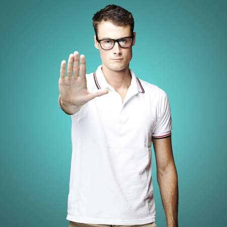 portrait of a young man doing stop gesture over blue background photo