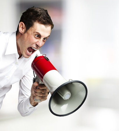 portrait of young man screaming with megaphone against a abstract background Stock Photo - 12656614