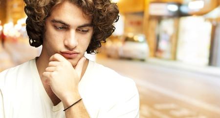 persona confundida: Primer plano de un joven pensando en un contexto noche de la ciudad