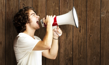 portrait of a handsome young man shouting with megaphone against a wooden wall photo