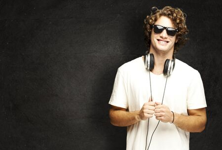 portrait of young man smiling with headphones against a grunge wall photo