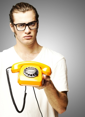 portrait of young man holding vintage telephone and doing good symbol over grey background photo