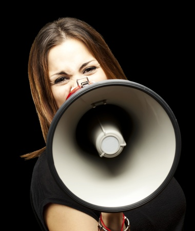 portrait of young woman shouting with megaphone over black Stock Photo - 12656516