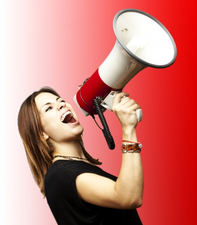 portrait of young girl shouting with megaphone over red background photo