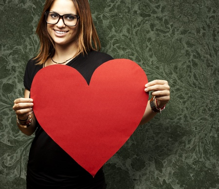 glass heart: portrait of a pretty woman holding a paper heart against a vintage wall