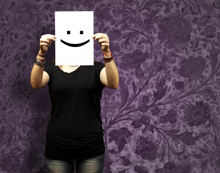 old sign: Woman showing a blank paper with a smile emoticon in front of her face against a vintage wall