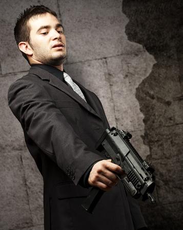 point and shoot: la mafia del hombre con la pistola apuntando hacia abajo contra un muro, cosecha,