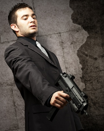 mafia man aiming down with gun against a vintage wall photo