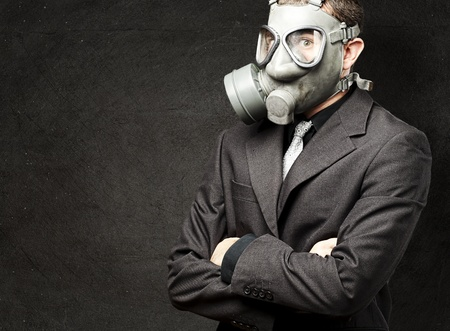 portrait of business man with gas mask against a grunge wall photo