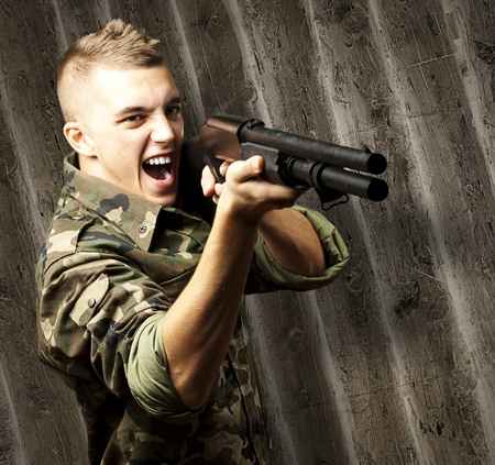 dirty blond: portrait of a young soldier aiming with shotgun against a wooden wall Stock Photo