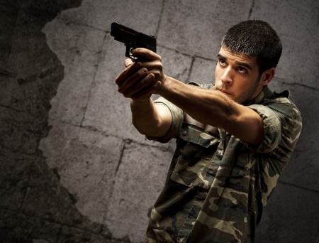 portrait of a young soldier aiming with pistol against a grunge bricks wall photo