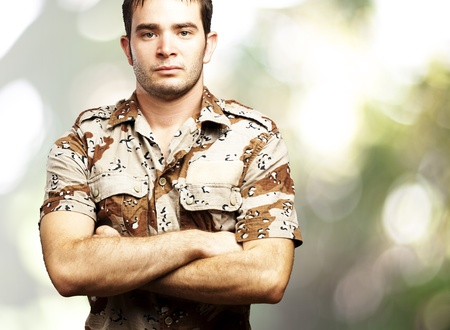 portrait of a serious young soldier standing against a nature background Stock Photo - 12656896