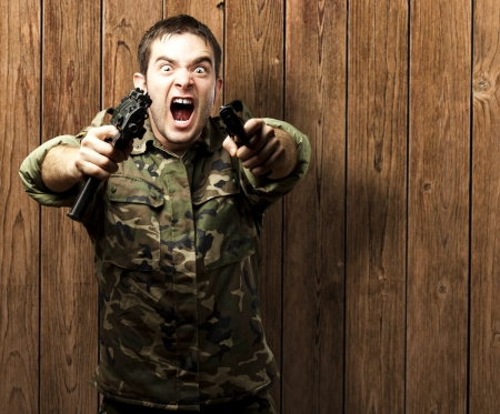 man holding gun: portrait of a young soldier aiming with pistol against a removable chroma key Stock Photo