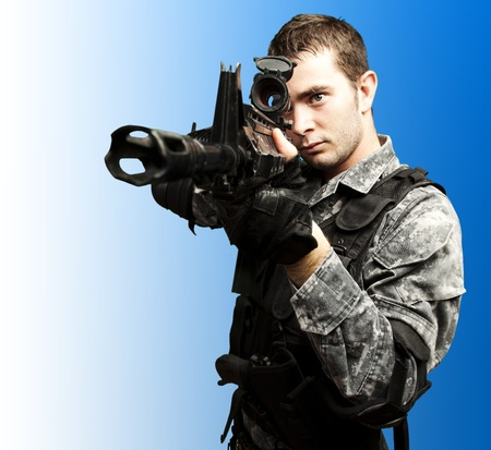 portrait of young soldier aiming with rifle over blue background Stock Photo - 12648044