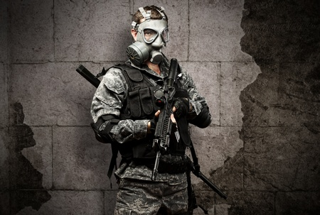 portrait of young soldier with gas mask and rifle against a grunge bricks background photo