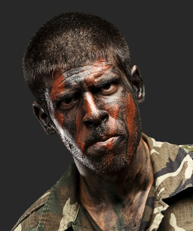 young soldier with camouflage paint looking very serious over black Stock Photo - 12656632