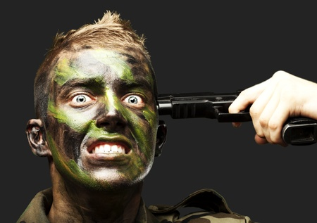portrait of young soldier comiting suicide over black background photo